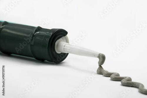 Leinwand Poster Silikonpistole mit ausgepressten grauen Silikon isoliert auf weiß