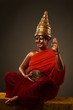 Pregnant woman with golden body art and hattery in buddha look