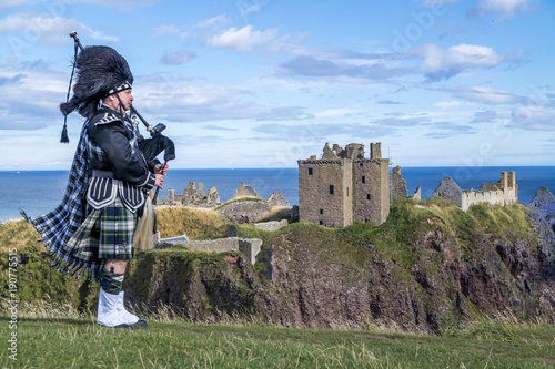 Photo Traditional scottish bagpiper in full dress code at Dunnottar Castle in Stonehav