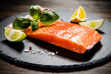 Fototapeta Fresh raw salmon fish served on black stone on wooden table