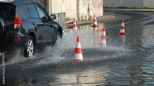Fotografía Voitures passant dans une rue inondée