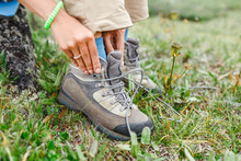 A Tourist Woman Ties Up Her Shoelaces On Trekking Boots, Outdoor Footwear Concept