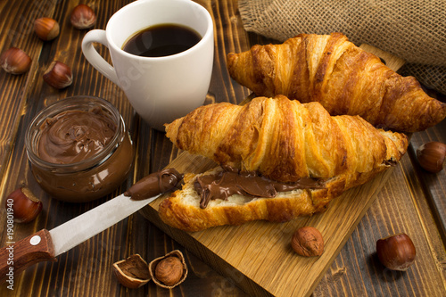 Fototapeta Croissants  with chocolate cream  and coffee on the rustic wooden background obraz