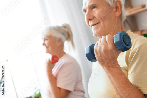 Senior couple exercise together at home health care with dumbbells ...