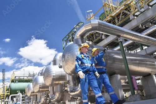 Staande foto Industrial geb. Arbeiter in einer Raffinerie - im Hintergrund Anlage zur Produktion von Treibstoff aus Erdöl - Industrieanlage mit Rohrleitungen // Workers in a refinery - industrial plant with pipelines