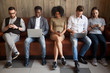 Leinwanddruck Bild - Multicultural young people using laptops and smartphones sitting in row, diverse african and caucasian millennials entertaining online obsessed with modern devices waiting in queue, gadget addiction