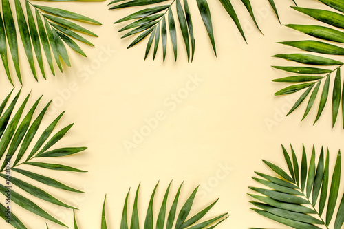 Poster Palmier Tropical green leaves palm fronds isolated on yellow background. the apartment lay, top view