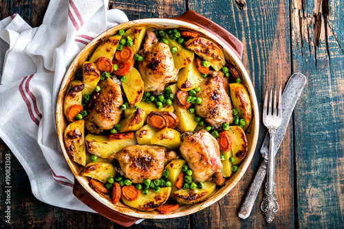 Fototapeta Chicken thighs baked with potato, carrot and green peas obraz