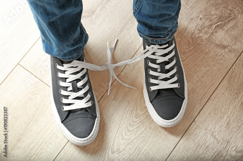Pinturas sobre lienzo  Man with shoelaces tied together. April fool's day prank