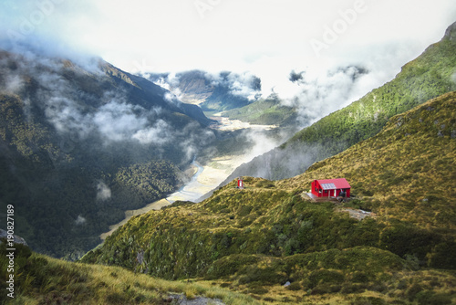 Valokuva  Liverpool Hut sits on the edge of a large cliff in the Matukituki Valley in Mt