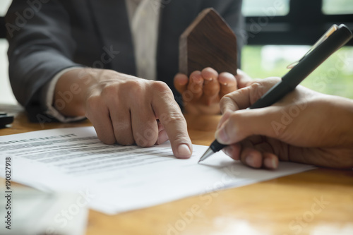 Photo  Close up of business person hand putting signing contract,running own small busi