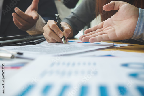 Photo  Close up business peple reaching out sheet with contract agreement proposing to sign