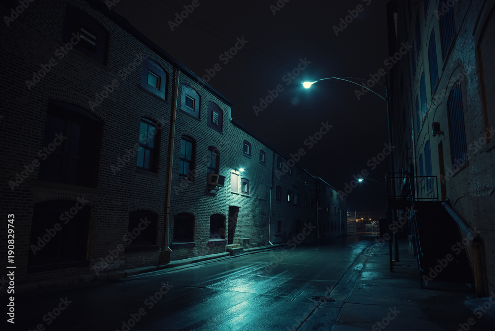 Fototapeta Dark urban city alley at night after a rain featuring vintage warehouses.
