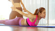 Trainer assisting woman on body stretching