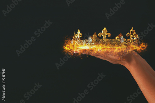 Fototapeta  Woman's hand holding a burning crown over black background.