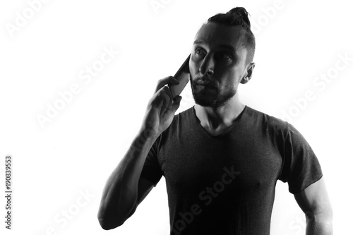 Fotografie, Obraz  Male person silhouette use mobile phone,,back lit isolated on white