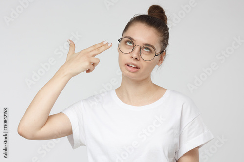 Fotografie, Obraz  Young woman committing suicide with finger gun gesture, shooting herself making