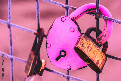 Fotografija  A pink heart-shaped love lock with baby lock