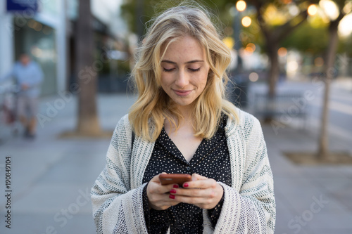 Photo  Young caucasian woman walking texting on cell phone