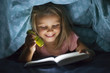canvas print picture - sweet beautiful and pretty little blond girl 6 to 8 years old under bed covers reading book in the dark at night with torch light smiling happy