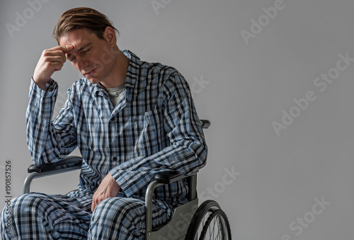 Valokuva  Portrait of depressed young man in chair with wheels unable moving by himself