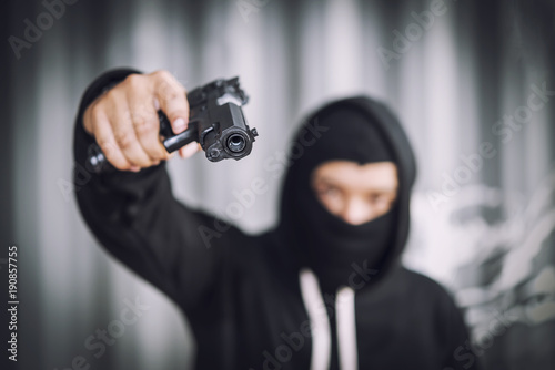 Fototapeta  Masked robber with gun aiming into the camera with monochrome background