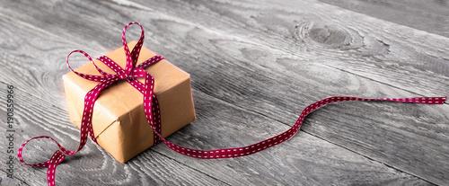 Fotografie, Obraz  Paket mit roter Schleife auf rustikalem Holz  --  Hintergrund, Banner
