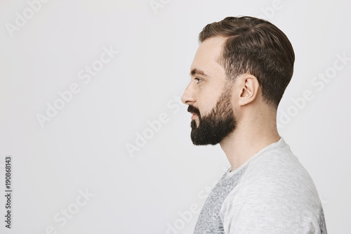 Profile portrait of handsome bearded adult european man with trendy  haircut, standing over gray background