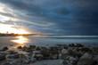 Sonnenuntergang am Strand mit Steinen, Palmen und dunklen Wolken in Kuba
