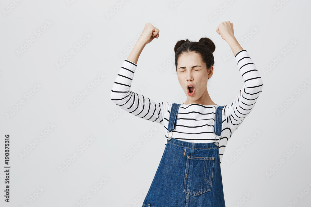 Valokuva  Brunette girl with hairbuns in striped top excited and glad to achieve victory, clenches fists, screams in excitement with closed eyes, happy to pass all exams at university, successful person