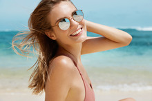 Close Up Shot Of Attractive Happy Female Spends Summer Vacation On White Beach At Exotic Island, Poses Against Ocean Background And Pure Blue Sky, Enjoys Nice Sunny Weather And Fresh Breeze.