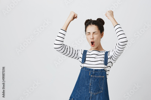 Fotografiet  Brunette girl with hairbuns in striped top excited and glad to achieve victory, clenches fists, screams in excitement with closed eyes, happy to pass all exams at university, successful person