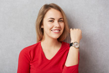 Happy Beautiful Woman With Pleasant Broad Smile Shows Her New Wristwatch, Being Delightful To Recieve It As Present From Boyfriend, Isolated Over Grey Background. People, Advertisment Concept
