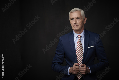 Fototapeta Confident businessman portrait. Executive senior lawyer businessman wearing suit and looking at camera while standing at isolated black background with copy space.  obraz