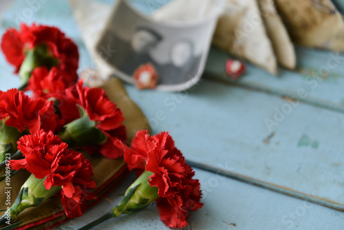 Fotografia  background for postcards by may 9, victory day: cap, letters, red carnations and St