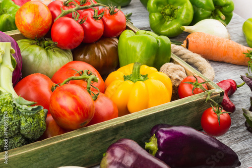 Fotografie, Obraz  Set of different fresh raw vegetables in the wooden tray, light background