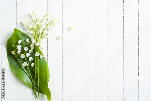 Staande foto Lelietje van dalen Lily of the valley on white wooden