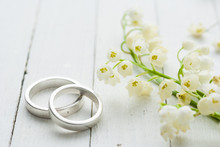 Lily Of The Valley With Wedding Rings On White Wooden