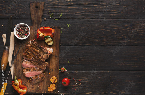 Spoed Foto op Canvas Vlees Grilled meat and vegetables on rustic wooden table