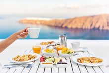 Breakfast Woman Drinking Coffee At Luxury Hotel Resort Restaurant Table Mediterranean Sea View In Santorini, Oia, Greece. Female Hand Holding Coffee Cup At Morning Brunch. Eggs, Fruit Salad Plate.