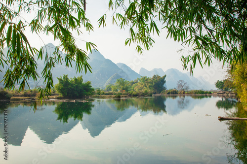 Spoed Fotobehang Reflectie Beautiful landscape of karst mountains reflected in water, Yulong river in Yangshuo South China.
