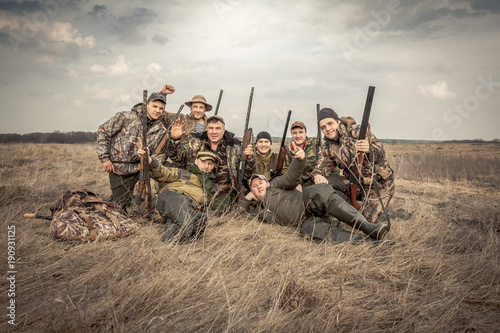 Poster Chasse Men hunters group team portrait in rural field posing together against overcast sky during hunting season. Concept for teamwork