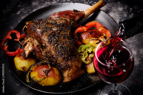 Roasted lamb shank with spices and grilled vegetables and red wine glass poured with wine