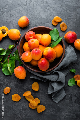 Photo Fresh apricots with leaves and dried in bowl on table