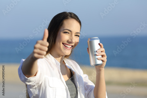 Woman holding a refreshment can looking at you on the beach