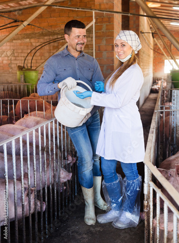 Fotografie, Obraz  Man and woman with feed for farm animals