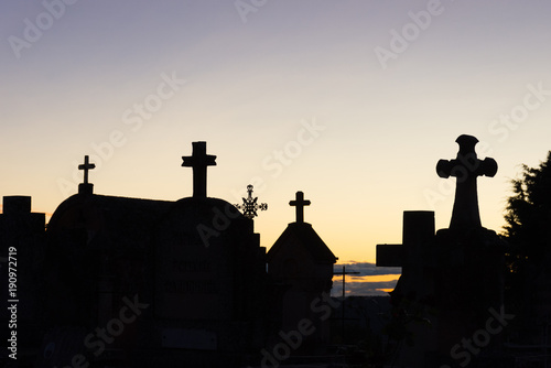 Keuken foto achterwand Begraafplaats Sunset at Roussillon's Cemetery with the silhouettes of the mausoleums topped with crosses against a yellow, gold and lavender sky.