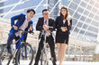 Asian young business group relax talking while riding bicycles in city