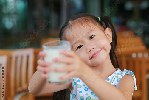 Smiling little asian girl drinking milk in restaurant at the morning.