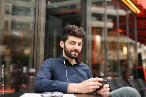Student Dressed In Blue Shirt Listening To Music With In Ear